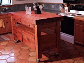 Custom mesquite chef's table with a 4 inch thick edge grain top, mortise and tenon jointery, and full extension drawers.