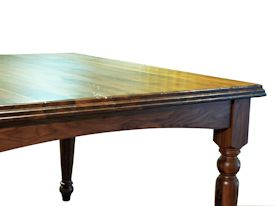 Custom distressed Walnut dining table with custom designed turned legs and arched aprons.