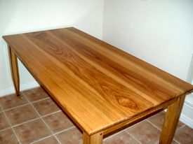 Custom face grain shaker style dining table with hand carved aprons and walnut accents on legs.